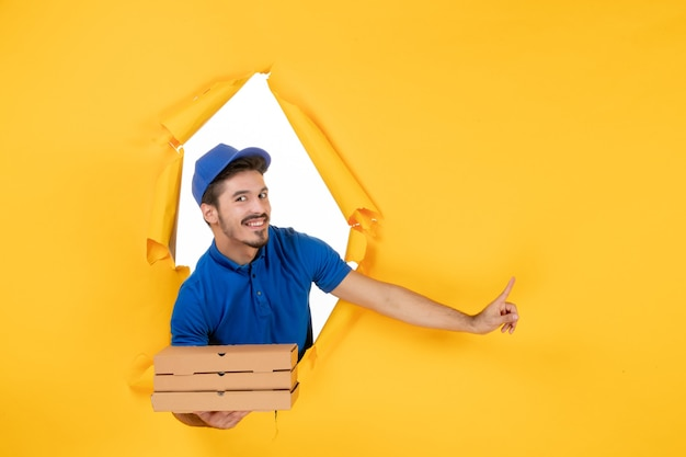 Männlicher kurier der vorderansicht, der pizzakartons auf gelbem raum hält