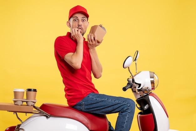 Männlicher kurier der vorderansicht, der wenig liefernahrungsmittel auf gelbem fahrradlieferungsfarbarbeitsarbeitsdienstnahrungsmittel hält