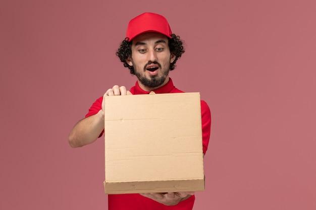 Männlicher kurier der vorderansicht im roten hemd und im umhang, der lieferung-nahrungsmittelbox hält und es auf der hellrosa wand öffnet