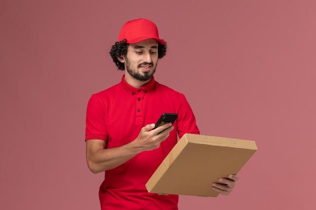 Männlicher kurier der vorderansicht im roten hemd und im umhang, die leere liefernahrungsmittelbox halten, die foto davon auf rosa wand macht
