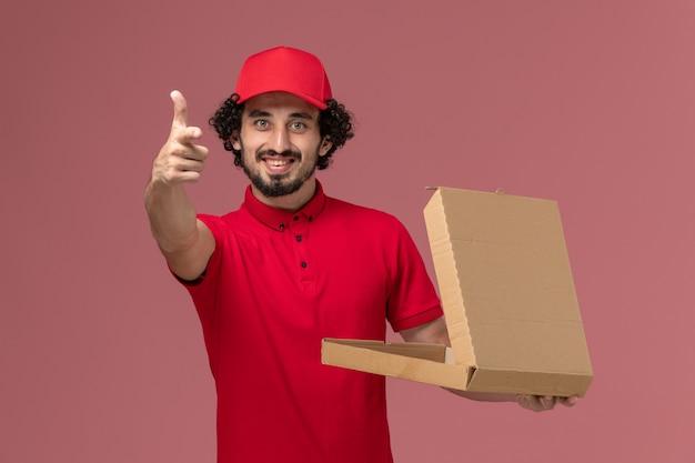 Männlicher kurier der vorderansicht im roten hemd und im umhang, die leere liefernahrungsmittelbox halten und auf rosa schreibtischdienstlieferungsmitarbeiter lächeln