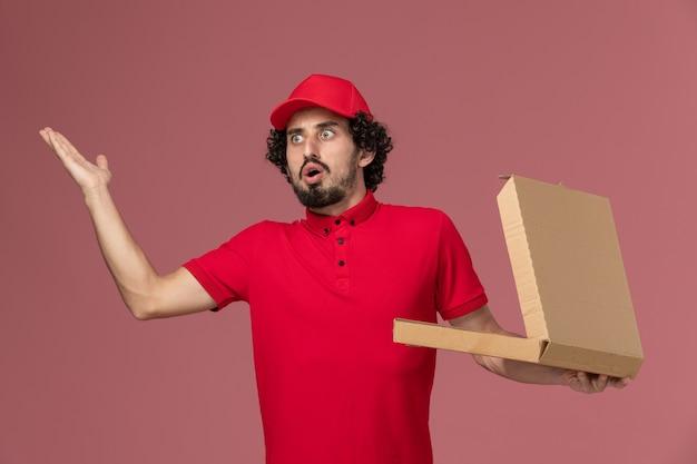 Männlicher kurier der vorderansicht im roten hemd und im umhang, die leere liefernahrungsmittelbox halten und auf rosa wand aufwerfen
