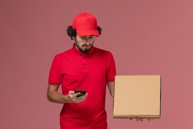 Männlicher kurier der vorderansicht im roten hemd und im umhang, die leere liefernahrungsmittelbox mit telefon auf rosa wand halten