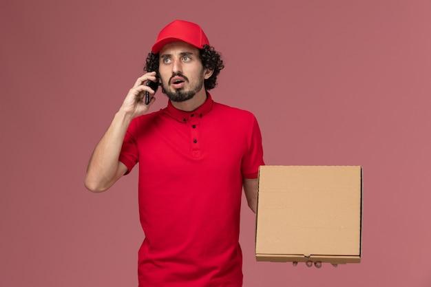 Männlicher kurier der vorderansicht im roten hemd und im umhang, die leere liefernahrungsmittelbox mit telefon halten, das auf rosa wand spricht