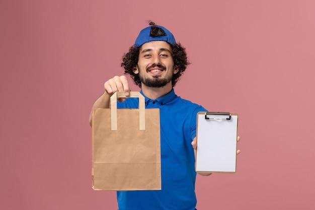 Männlicher kurier der vorderansicht in blauer uniform und umhang, der lieferpapiernahrungsmittelpaket und -block auf rosa wandlieferdienstuniform hält