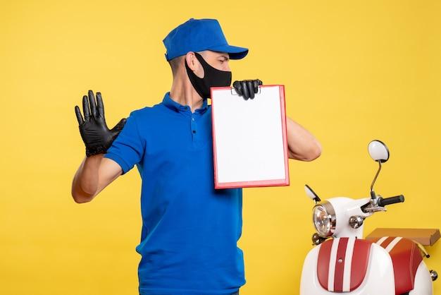 Männlicher kurier der vorderansicht in der blauen uniform, die aktennotiz auf einer gelben arbeitsdienst-pandemie-lieferpandemie-farbuniform hält