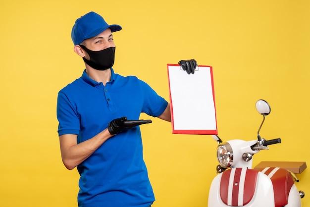 Männlicher kurier der vorderansicht in der blauen uniform, die aktennotiz auf gelber arbeitsdienst-covid-delivery-farbuniformarbeit hält
