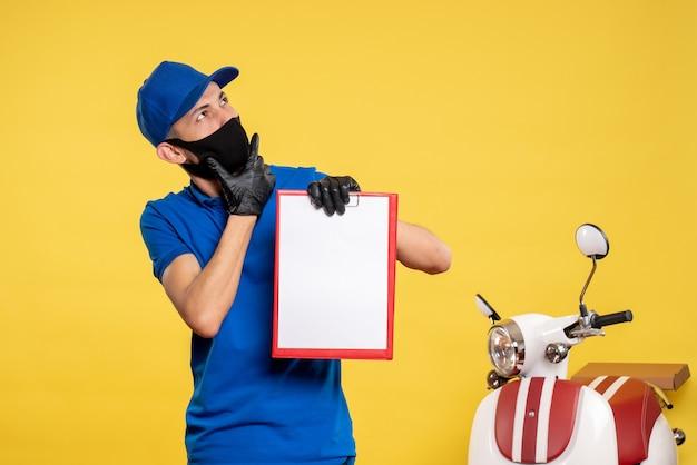Männlicher kurier der vorderansicht in der blauen uniform, die aktennotiz auf gelber arbeitsdienst-covid-delivery-pandemie-farbuniformarbeit hält