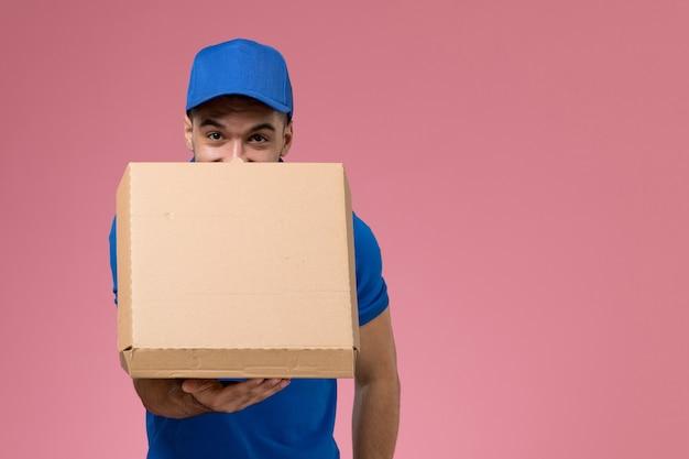 Männlicher kurier der vorderansicht in der blauen uniform, die die öffnende nahrungsmittelbox an der rosa wand hält, einheitliche dienstauftragslieferung
