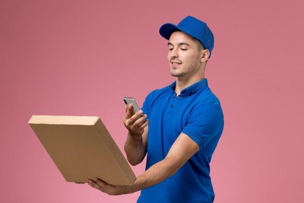 Männlicher kurier der vorderansicht in der blauen uniform, die ein foto der nahrungsmittelbox mit lächeln auf rosa wand, dienstuniform-dienstlieferung des arbeiters macht