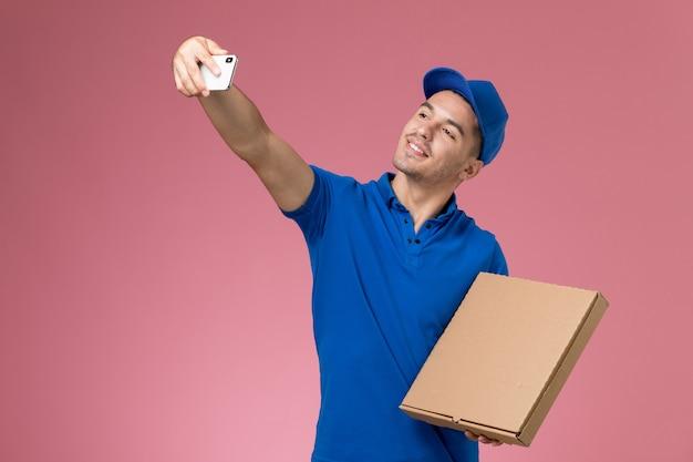 Männlicher kurier der vorderansicht in der blauen uniform, die ein foto mit lebensmittelbox auf rosa wand, dienstuniform-dienstlieferung des arbeiters macht