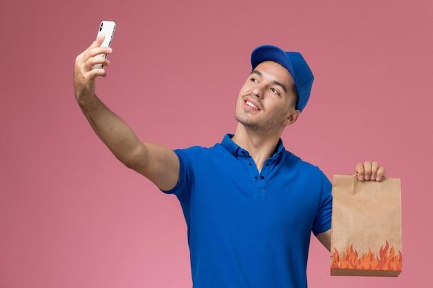 Männlicher kurier der vorderansicht in der blauen uniform, die foto mit lebensmittelpaket auf der rosa wand, dienstuniform-dienstlieferung des arbeiters nimmt