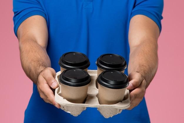 Männlicher kurier der vorderansicht in der blauen uniform, die kaffeetassen auf rosa, arbeiteruniform-dienstlieferung liefert