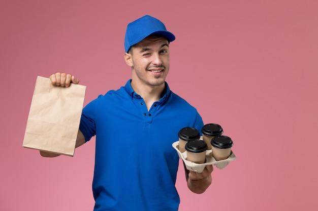 Männlicher kurier der vorderansicht in der blauen uniform, die kaffeetassen der lebensmittelverpackung an der rosa wand hält, einheitlicher dienstlieferungsarbeiter