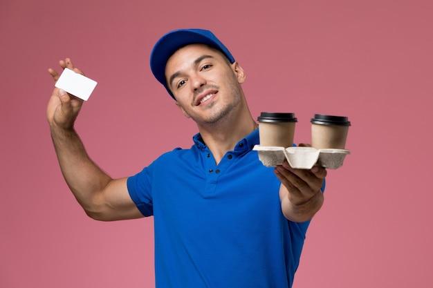 Männlicher kurier der vorderansicht in der blauen uniform, die kaffeetassen der weißen karte an der rosa wand hält, dienstarbeiteruniformdienstlieferung