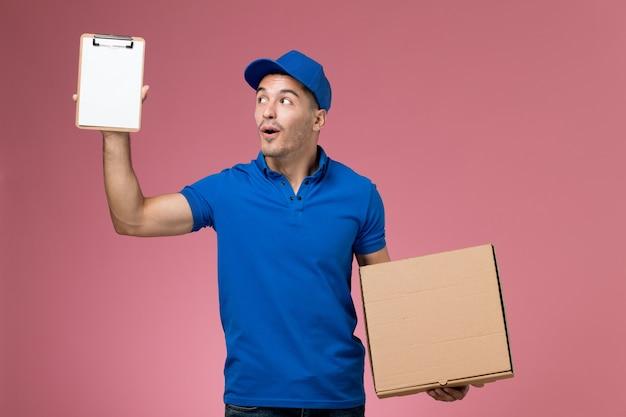 Männlicher kurier der vorderansicht in der blauen uniform, die kleinen notizblock und nahrungsmittelkasten an der rosa wand hält, arbeitsuniform-dienstlieferung