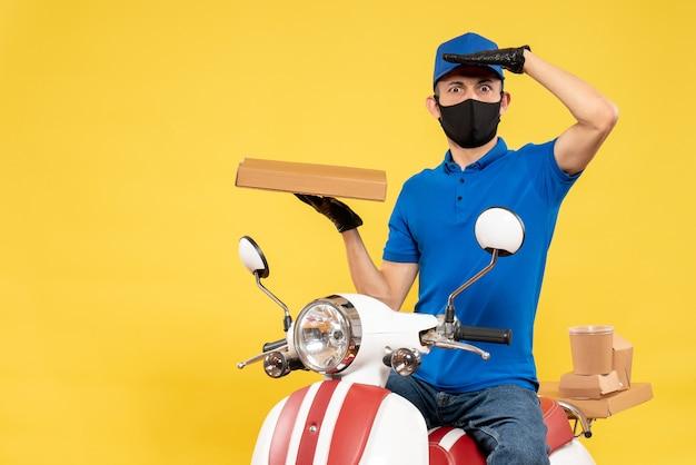 Männlicher kurier der vorderansicht in der blauen uniform, die lebensmittelbox auf einem gelben pandemie-fahrrad-covid-delivery-virus-arbeitsservicejob hält