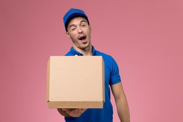 Männlicher kurier der vorderansicht in der blauen uniform, die lebensmittelbox hält, die an der rosa wand zwinkert, einheitliche dienstauftragszustellung