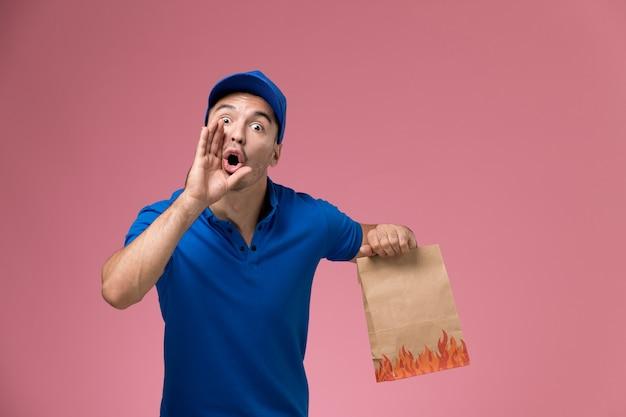 Männlicher kurier der vorderansicht in der blauen uniform, die lebensmittelpaket hält und auf rosa wand schreit, dienstarbeiteruniformdienstlieferung
