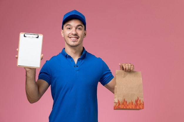 Männlicher kurier der vorderansicht in der blauen uniform, die lebensmittelpaket mit notizblock an der rosa wand hält, arbeitsuniformuniformdienstlieferung