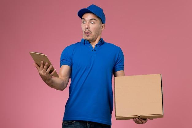 Männlicher kurier der vorderansicht in der blauen uniform, die nahrungsmittelbox mit notizblock auf der rosa wand hält, arbeitsuniform-dienstlieferung