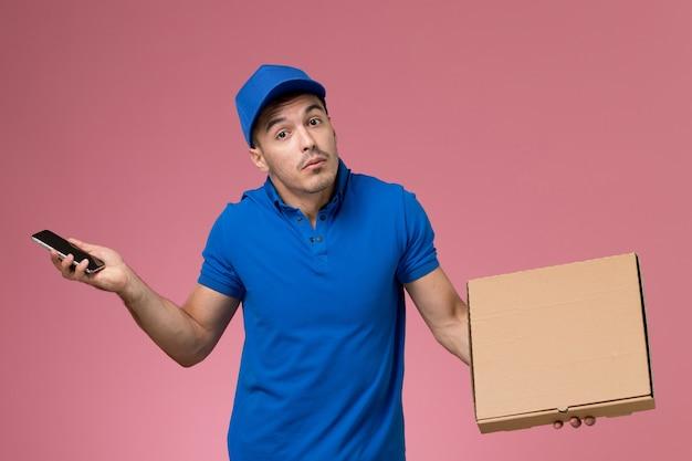Männlicher kurier der vorderansicht in der blauen uniform, die nahrungsmittelbox mit telefon an der rosa wand hält, uniformdienstlieferant