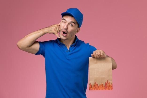 Männlicher kurier der vorderansicht in der blauen uniform, die nahrungsmittelpaket an der rosa wand hält, arbeitsdienstuniformuniversitätslieferung