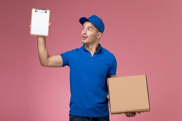 Männlicher kurier der vorderansicht in der blauen uniform, die notizblock mit nahrungsmittelbox auf der hellrosa wand hält, arbeitsuniform-dienstlieferung