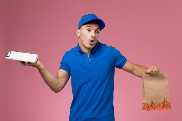 Männlicher kurier der vorderansicht in der blauen uniform, die notizblock-nahrungsmittelpaket an der rosa wand hält, einheitliche dienstauftragszustellung