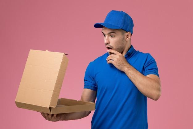 Männlicher kurier der vorderansicht in der blauen uniform, die öffnende nahrungsmittellieferbox an der rosa wand hält, einheitliche dienstauftragslieferung