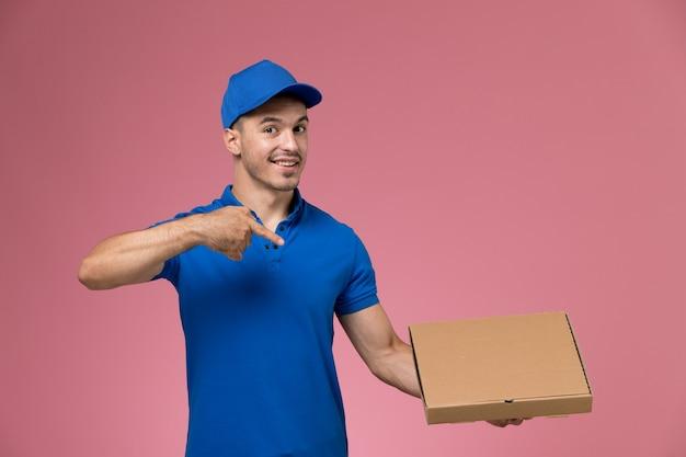Männlicher kurier der vorderansicht in der blauen uniform, die öffnende nahrungsmittellieferbox an der rosa wand hält, einheitliche jobdienstlieferung