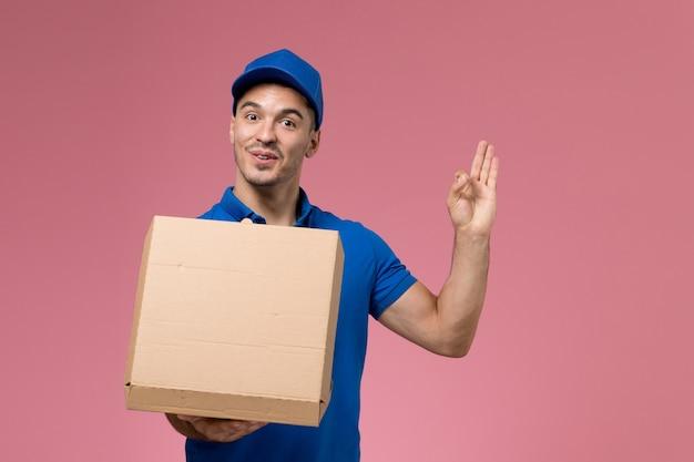 Männlicher kurier der vorderansicht in der blauen uniform, die öffnende nahrungsmittellieferbox auf rosa wand hält, einheitliche dienstlieferung