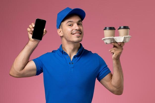 Männlicher kurier der vorderansicht in der blauen uniform, die sein telefon und kaffeetassen an der rosa wand hält, einheitliche dienstauftragszustellung