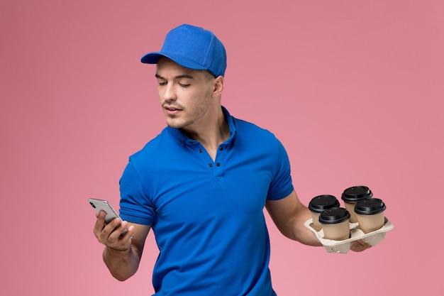Männlicher kurier der vorderansicht in der blauen uniform, die sein telefon und kaffeetassen auf rosa wand hält, einheitliche servicebereitstellung