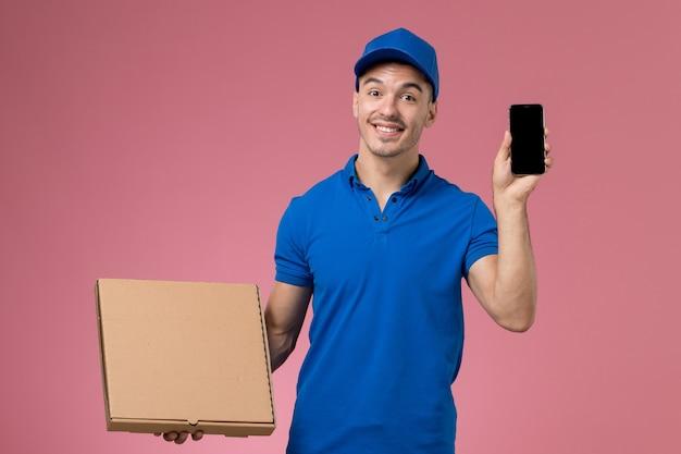 Männlicher kurier der vorderansicht in der blauen uniform, die telefon und lebensmittelbox mit lächeln auf rosa wand hält, einheitliche servicebereitstellung