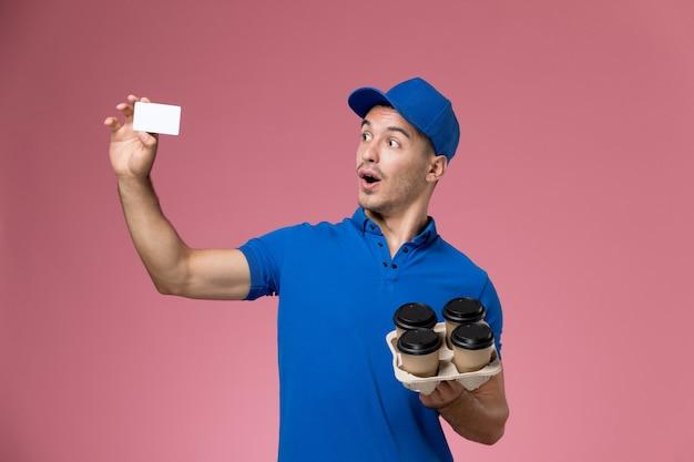 Männlicher kurier der vorderansicht in der blauen uniform, die weiße karte und lieferkaffeetassen auf rosa wand hält, einheitliche jobarbeiterdienstlieferung