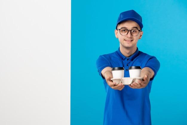 Männlicher kurier der vorderansicht in der blauen uniform mit kaffee auf einem blau
