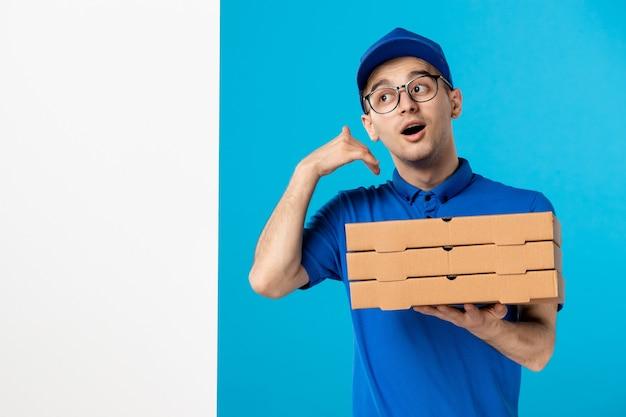 Männlicher kurier der vorderansicht in der blauen uniform mit pizzaschachteln auf einem blau