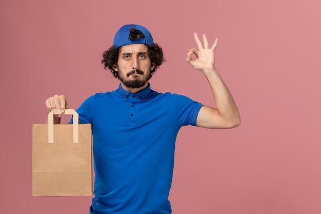 Männlicher kurier der vorderansicht in der blauen uniform und im umhang, der lieferpapiernahrungsmittelpaket auf rosa wandarbeitslieferdienstjobuniform hält