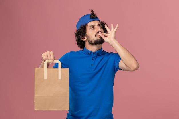 Männlicher kurier der vorderansicht in der blauen uniform und im umhang, der lieferpapiernahrungsmittelpaket auf rosa wandarbeitslieferdienstuniform hält