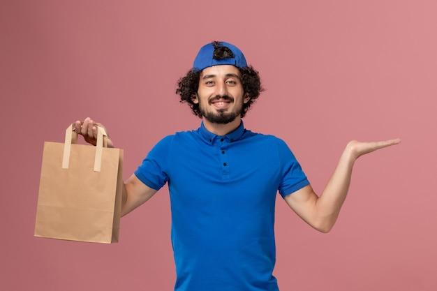 Männlicher kurier der vorderansicht in der blauen uniform und im umhang, der lieferpapiernahrungsmittelpaket auf rosa wandlieferdienstuniformarbeit hält