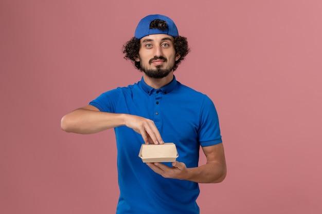 Männlicher kurier der vorderansicht in der blauen uniform und im umhang, die kleines liefernahrungsmittelpaket an der rosa wand halten