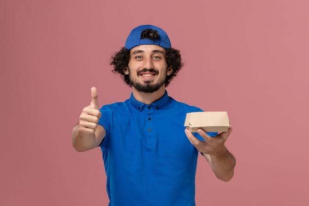 Männlicher kurier der vorderansicht in der blauen uniform und im umhang, die kleines liefernahrungsmittelpaket auf rosa wanduniform-zustelldienstmitarbeiter halten
