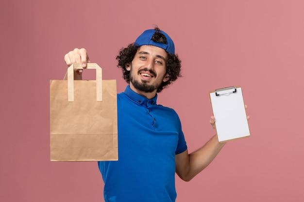 Männlicher kurier der vorderansicht in der blauen uniform und im umhang, die lieferpapiernahrungsmittelpaket und -block auf rosa wandlieferdienstuniform-arbeitsmann halten