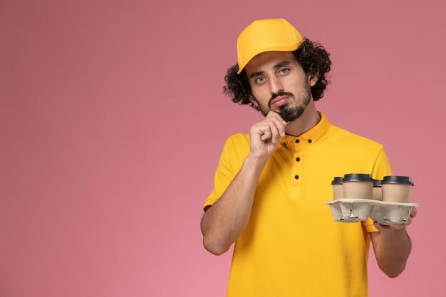 Männlicher kurier der vorderansicht in der gelben uniform, die braune kaffeetassen der lieferung hält, die an rosa wand denken