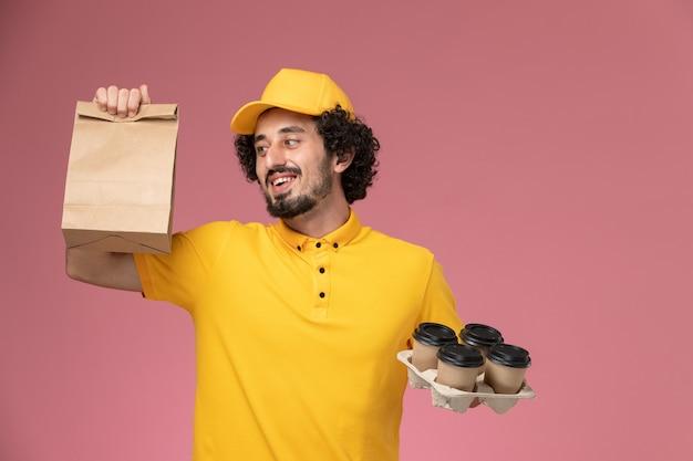 Männlicher kurier der vorderansicht in der gelben uniform, die braune kaffeetassen und lebensmittelverpackung der lieferung an der rosa wand hält