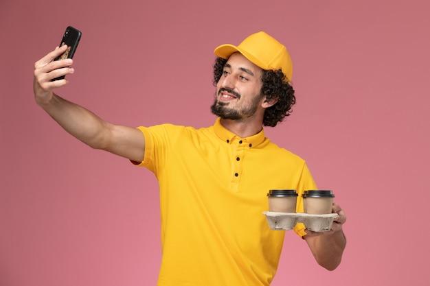 Männlicher kurier der vorderansicht in der gelben uniform, die braune lieferkaffeetassen hält, die foto auf rosa wand nehmen