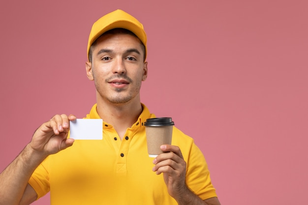 Männlicher kurier der vorderansicht in der gelben uniform, die die kaffeetasse der lieferung und die weiße karte auf dem rosa hintergrund hält