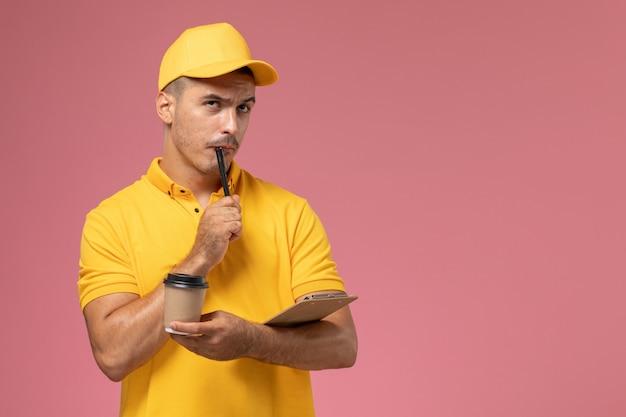Männlicher kurier der vorderansicht in der gelben uniform, die die kaffeetasse hält, die notizen auf rosa hintergrund schreibt