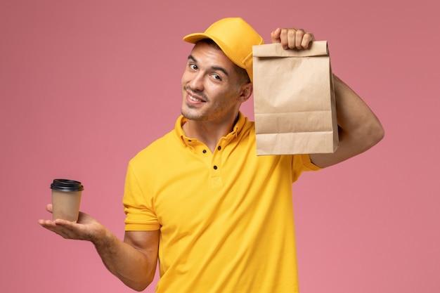 Männlicher kurier der vorderansicht in der gelben uniform, die die kaffeetasse und das lebensmittelpaket der lieferung auf dem hellrosa schreibtisch hält